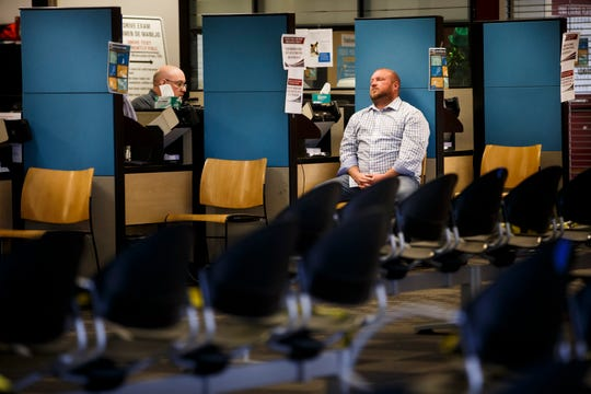 In front of an empty waiting room, Scott Thomas of Des Moines waits for a photo Wednesday at the Iowa Department of Transportation office in Ankeny. The department has gone to an appointment-only system for people needing to use its services in an effort to help stop the spread of COVID-19.