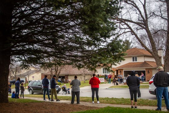 Neighbors come to listen as the band Opus Taylor plays in their Clive neighborhood while encouraging listeners to practice social distancing Wednesday, March 25, 2020.