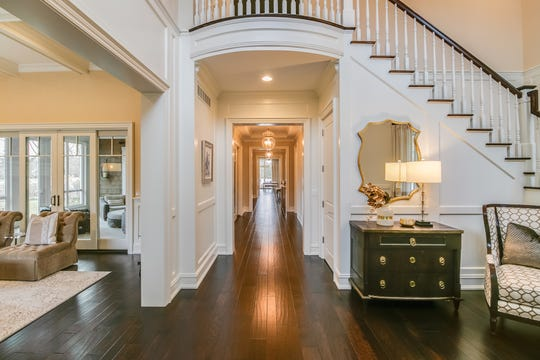 Step into the front foyer and you're looking down a long hall the depth of the house, dramatic with a dark wood floor and white walls. At the end of the hall glass doors open to the outdoor room in the back yard.