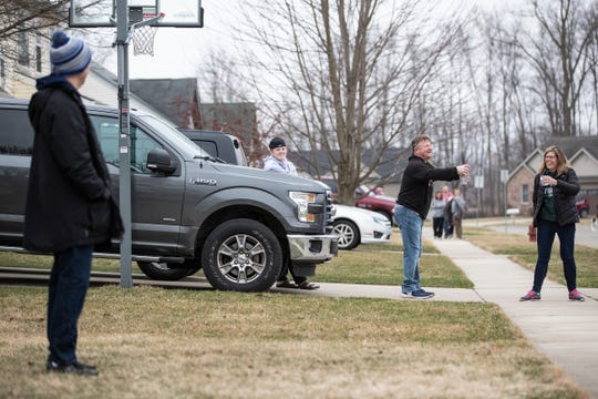 Milan mayor Dominic Hamden, left, stands in front of his home in Milan as he talks to neighbors Daniel Runkel, 16, his father Dave and mother Molly on March 24, 2020.