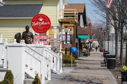 People walk along S. Main St. in Frankenmuth as businesses remain closed on March 25, 2020, due to the stay-at-home order to help prevent the spread of COVID-19.