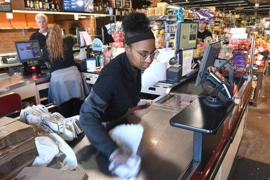 Malaysia Search, cashier, cleans and sterilizes her register area at Fresh Farms Market in Grosse Pointe.