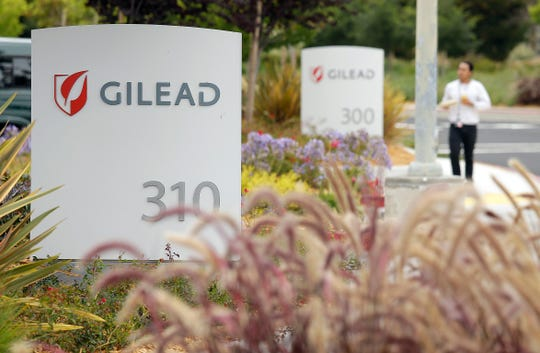 FILE - In this July 9, 2015, file photo, a man walks outside the headquarters of Gilead Sciences in Foster City, Calif.