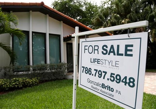 In this Aug. 15, 2015, file photo, a for sale sign is placed in front of a home in Miami.  On Wednesday, March 25, economists are waiting for the first signs of virus-related disruptions in housing with the expectation that they will be seismic.
