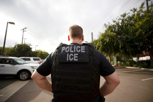 In this July 8, 2019, file photo, a U.S. Immigration and Customs Enforcement (ICE) officer looks on during an operation in Escondido, Calif.  Pressure is mounting on the Trump administration to release people from immigration detention facilities where at least one detainee has already tested positive for COVID-19.