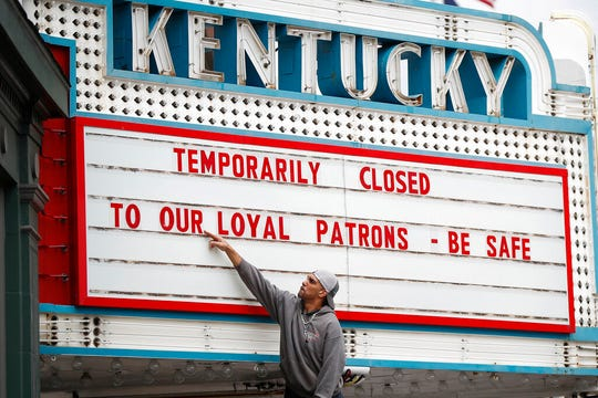 Harry Powell works to change the marquee at the Kentucky Theatre in Lexington, Kentucky. The Kentucky Theatre will close on Wednesday following an executive order from Gov. Andy Beshear asking all public-facing businesses to close to help fight the spread of coronavirus.