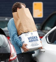 "A shopper struggles to open the back door of his sedan while juggling his purchase from a liquor store minutes after Denver Mayor Michael hancock issued a ""stay at home"" order to reduce the spread of the new coronavirus Monday, March 23, 2020, in Denver."