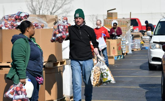 From left, Verly Sutton, 49, and T.J. Robinson, 41, both of Detroit and with Gleaners, move food to the vehicles and walk up residents. Gleaners Community Food Bank operates a drive thru and walk up food drive in Southwest Detroit near the Clemente Recreation Center in Detroit on Mar. 25, 2020.