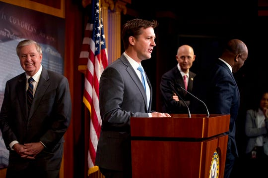 Sen. Ben Sasse, R-Neb., center, accompanied by Sen. Lindsey Graham, R-S.C., left, Sen. Tim Scott, R-S.C., right, and Sen. Rick Scott, R-Fla., second from right, speaks at a news conference about the coronavirus relief bill at a news conference on Capitol Hill in Washington, Wednesday, March 25, 2020.