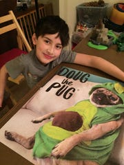 Ginny Grush's grandson, Vincent, with a completed puzzle.
