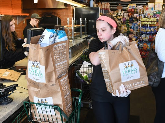 Claire Dalian, cashier, prepares items for pick up and delivery at Fresh Farms Market in Grosse Pointe.