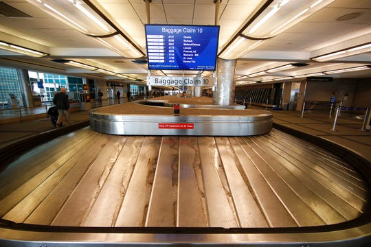 In this March 20, 2020 file photo, an empty baggage carousel spins in Denver International Airport as travelers deal with the spread of the coronavirus  in Denver.  Airline service in the United States is teetering on the brink of collapse, with near-empty planes and coronavirus-caused outbreaks that have left some air traffic control towers empty.