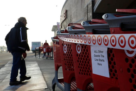 A sign displays outside of a Target store in Glenview, Ill., Wednesday, March 25, 2020. Grocery store chains and other retailers began offering special shopping hours for seniors and other groups considered the most vulnerable to the new coronavirus.