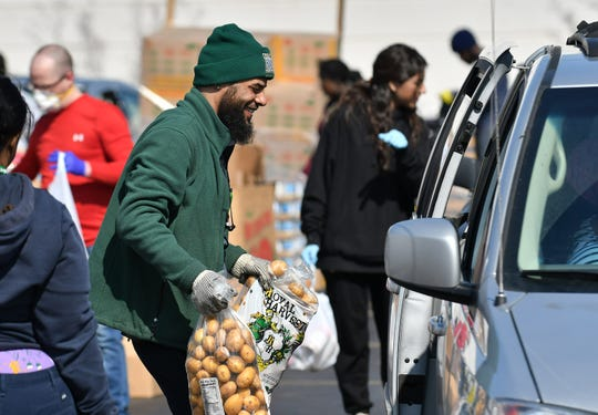 Andre Peterson, 36, of Harper Woods gets bags of potatoes to a family's vehicle. Gleaners Community Food Bank operates a drive thru and walk up food drive in Southwest Detroit near the Clemente Recreation Center in Detroit on Mar. 25, 2020.