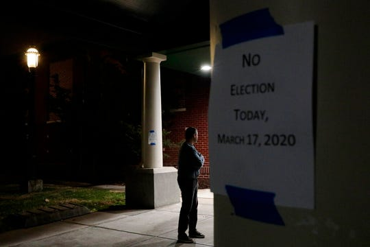 In this March 17, 2020, file photo a man, who hoped to vote in the scheduled primary election, stands outside a closed polling station at Schiller Recreation Center in Columbus, Ohio. U.S. elections have been upended by the coronavirus pandemic.