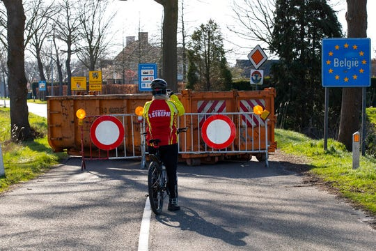 A cyclists takes images of a barricaded backroad used by locals on the Netherlands border with Belgium between Chaam, southern Netherlands, and Meerle, northern Belgium, Monday, March 23, 2020. Both countries have come to a near standstill as their governments sought to prevent the further spread of coronavirus.