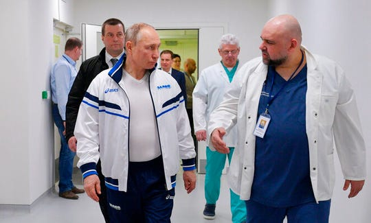 Russian President Vladimir Putin, center, and the hospital's chief Denis Protsenko, right, walk in to the hospital for coronavirus patients in Kommunarka settlement, outside Moscow, Russia, Tuesday, March 24, 2020.