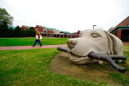 In this March 24, 2020, photo, a woman walks past a dog sculpture on the campus of the North Carolina State University College of Veterinary Medicine in Raleigh, N.C. The school is one of several vet schools around the country that have donated breathing machines, masks and other supplies to their human health-care counterparts in the fight against the COVID-19 pandemic.