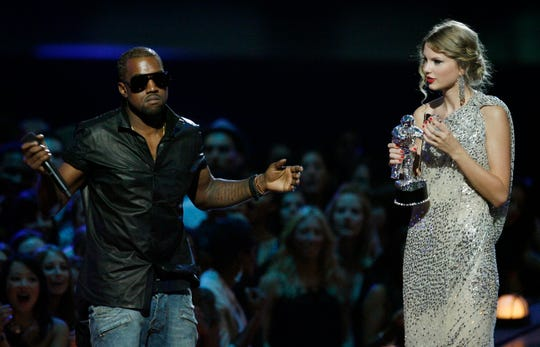 """FILE - In this Sept. 13, 2009 file photo, singer Kanye West takes the microphone from singer Taylor Swift as she accepts the """"Best Female Video"""" award during the MTV Video Music Awards in New York."""