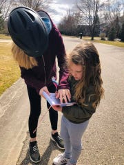 Josie Hoover, right, and her sister, Kenley, of Commerce Township keep track of how many shamrocks they find during their subdivision's Shamrock Walk. They found 51.