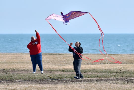 Andrea Gordon and her son, Jaden Gordon, 10, both of Clinton Twp., fly their dragon kite near the beach at Lake St. Clair Metropark, in Harrison Twp. on March 25, 2020.