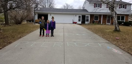 """Dylan, Ally and Emma Elliot are pictured waiting outside for the Pier Elementary School parade on Tuesday, March 24, 2020. The children wrote """"Pier Rocks"""" on their driveway to show school pride."""