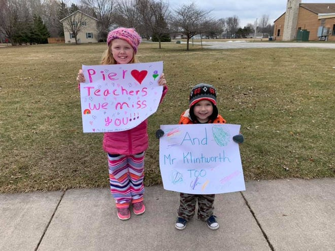 Addison and Paxton Brester made signs to greet Pier Elementary School staff as they drove by in their car parade held Tuesday, March 24, 2020.