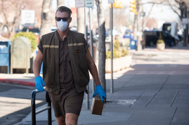 A UPS worker wears a mask and gloves as he makes his deliveries in Old Town as companies respond to the coronavirus pandemic in Fort Collins, Colo. on Tuesday, March 24, 2020.