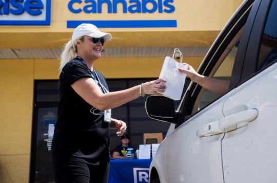 "Ashley Alto, a shift supervisor for Rise Cannabis in Bonita Springs delivers product to a customer on Wednesday March 25, 2020. The  company is staying open amid the coronavirus pandemic. They are offering ""herb-side pickup"" to customers"