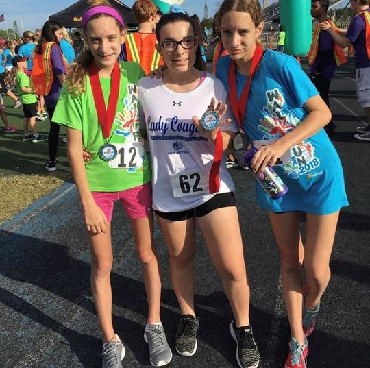 Becca Pacter, center, poses with friends at a running event. She is heading to Cottey College in Nevada, Missouri  this fall for her first year of college.