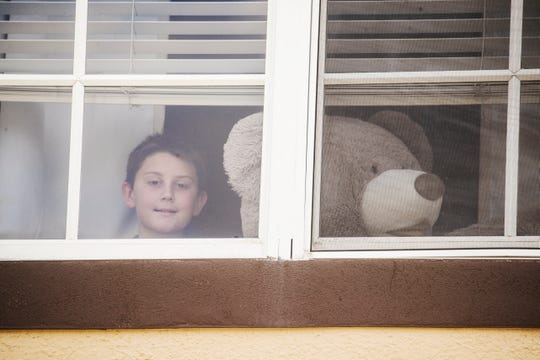 Cape Coral resident Tanner Trepkowski, 11, poses with a stuffed bear in his home on Wednesday March 25, 2020. At least a dozen members of his community have placed stuffed bears or stuffed animals so children in the neighborhood can go on a bear hunt. The idea is have activities for the children and to distract them from all the coronavirus pandemic worries.