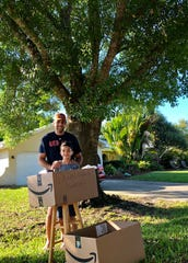 Vik Chhabra and his 7-year-old son Ethan before a box of food donated by neighbors for a micro-food drive Chhabra hosted in his driveway Tuesday, March 24, 2020, to help his church restock area food pantries.