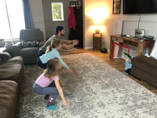 Tyler Krueger, with help from his daughters, Larkin, 6, and Sloane, 8, leads an at-home gym webinar for kids from his living room in De Pere. Krueger and his wife, Hilary, decided to start the online class after schools were closed due to the coronavirus pandemic.