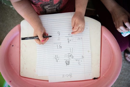 Winter Henderson, 5, practices her math while home from school as a result of the coronavirus outbreak, Wednesday, March 25, 2020. Her mother, Summer Easter, a single mother and a cook at Sidewall Pizza in Travelers Rest, has been unable to work as a result of the outbreak. The restaurant donated 100% of their $51,000 in gift cards sales on Wednesday through Friday of last week to their employees.