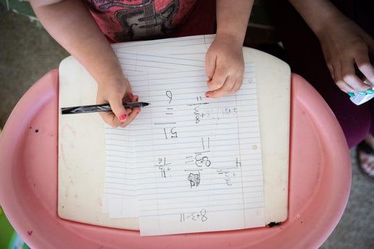 Winter Henderson, 5, hace tarea en su casa a causa del brote del coronavirus en el 25 de marzo, 2020.
