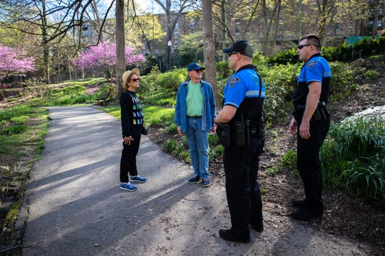 Officers Strange and Bixby with the Greenville city police department inform visitors to Falls Park in downtown Greenville of the temporary closure of the park, Wednesday, March 25, 2020. The closure went into effect on Monday.