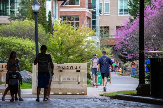Visitors to downtown Greenville walk through Falls Park Wednesday, March 25, 2020, after enforcement of the temporary closure of the park which went into effect on Monday began.