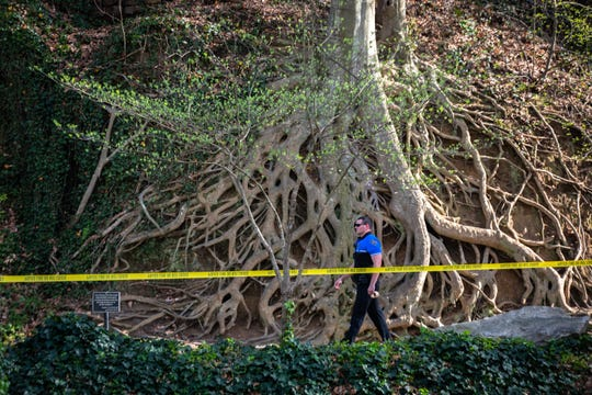 A Greenville city police officer walks through Falls Park in downtown Greenville Wednesday, March 25, 2020, as enforcement of the temporary closure of the park which went into effect on Monday begins.