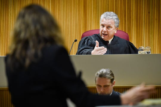 FILE - In this Jan.8, 2020 file photo Montana Supreme Court Justice Dirk Sandefur, right, questions Maureen Lennon, attorney for the Montana Association of Counties, arguing on behalf of the Lincoln County Sheriff in Helena, Mont., during arguments on whether local law enforcement officers have the authority to arrest people for alleged civil violations of federal immigration law. The Montana Supreme Court ruled Wednesday, March 25, 2020, that state and local law enforcement officers don't have the authority to arrest people on federal civil immigration detention requests. (Thom Bridge/Independent Record via AP, File)