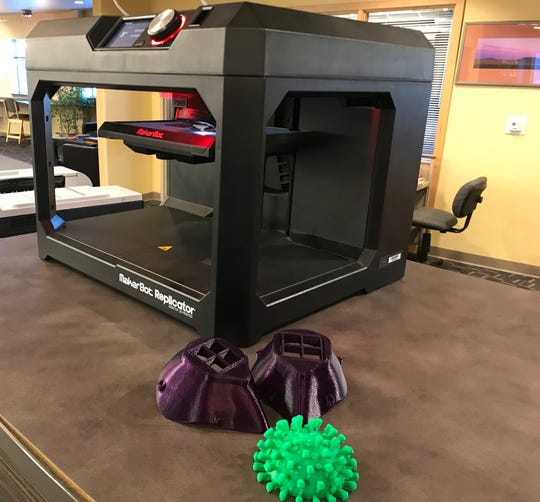 The 3D printer at Weaver Library on the campus of Great Falls College MSU is working overtime to produce masks for health care workers. Two masks, which still need a filter and strap, sit in the foreground with a model of the coronavirus that the library staff members printed a few weeks ago.
