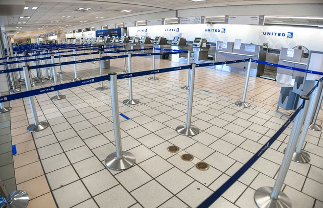 Stanchions normally used to manage a crowd of travelers departing on United Airlines flights at the A.B. Won Pat International Airport are  void of passengers in this March 25 file photo.
