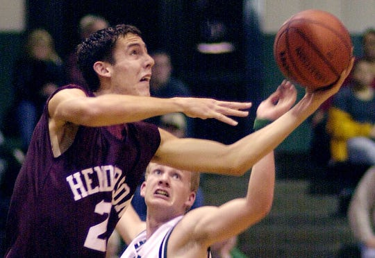 HCHS's Russ Gibson (20) tries to lay the ball in from under the goal as North's Garth Cheek (30) comes in behind during their game at North High School Friday night, December 14, 2001. (Gleaner photo by Darrin Phegley)