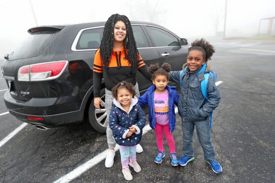 Jasmine Anderson, from left, poses with her kids Trenadi Elliott, Kennadi Elliott, and Antwoine Elliott before dropping them off to day care at the Freedom Academy Childcare Ministry at The Reset Center, Wednesday, March 25, 2020.