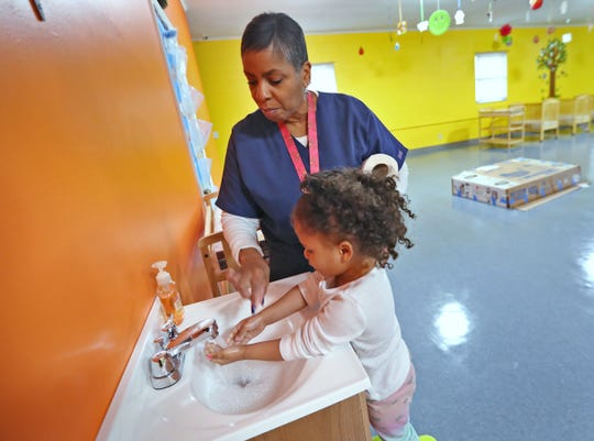 Freedom Academy Childcare Ministry Director Gina Harding helps Trenadi Elliott wash her hands at The Reset Center, Wednesday, March 25, 2020.  That's the first job after taking their coats off.  Trenadi and her siblings were dropped off for day care by their mom, Jasmine Anderson, not pictured.