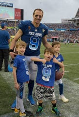 NFC quarterback Drew Brees (9), of the New Orleans Saints and his sons, are seen on the sidelines, during the second half of the NFL Pro Bowl football game against the AFC, Sunday, Jan. 28, 2018, in Orlando, Fla.