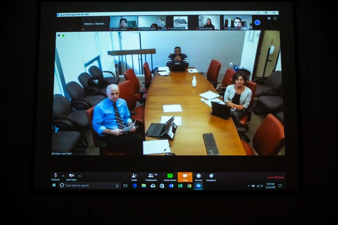 Bruce Teague, mayor of Iowa City, center, is seen talking on a Zoom conference call during a city council work session with city manager Geoff Fruin, left, and city attorney Eleanor M. Dilkes, Tuesday, March 24, 2020, at City Hall in Iowa City, Iowa.