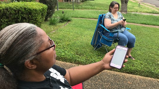 Clinton resident Belinda Woods-Johnson, left, looks at the call log on her cell phone on Wednesday morning. She and neighbor, Darla Kemmerer, right, have made repeated attempts to get through a busy unemployment phone line. Wednesday, March 25, 2020.