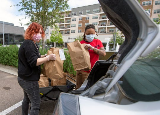 Fine & Dandy employees Sarah Waters, left, of Jackson, and Skylar Purvis, of Ridgeland, load an order of groceries into a car at the pick up location set up between Fine & Dandy and Sophomore Spanish Club Wednesday, March 25, 2020.