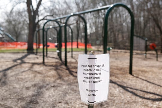 """A sign is posted at the Happy Hollow Park playground advising the closure """"due to the Covid-19 pandemic,"""" Wednesday, March 25, 2020 in West Lafayette."""