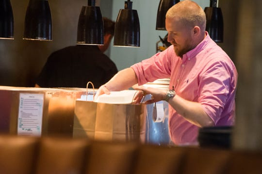 Brian Thom preparing to-go orders at SOCIAL Southern Table and Bar on Johnston St.  Wednesday, March 25, 2020.